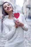 Closeup portrait amazing girl in the white warm woolen sweater with gray silver hair with red and white lollipop Royalty Free Stock Images
