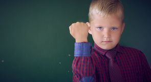 Closeup portrait of angry Caucasian boy showing fist, demanding justice, his rights. Boy isolated green wall background. stock image