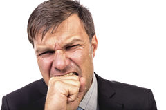 Closeup portrait of an angry guy biting his fist Stock Photography