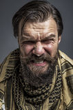 Closeup portrait of an angry man with beard wearing a traditiona Royalty Free Stock Photo