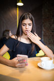 Closeup portrait anxious young girl looking at phone seeing bad news or photos with disgusting emotion on her face isolated cafe b stock image