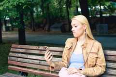 Young blonde woman looking at her smartphone and thinks who is colling. Negative reaction to the call royalty free stock photos