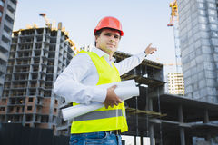 Closeup portrait of architect in hardhat showing building Stock Photos