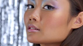 Thai asian model in studio with silver rain disco background and party makeup. Closeup portrait of asian model with ideal skin, wears holographic eyeshadow stock video footage