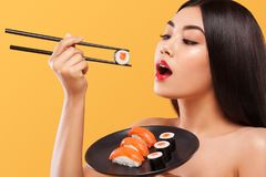 Closeup portrait of asian woman eating sushi and rolls on a yellow background. Stock Images