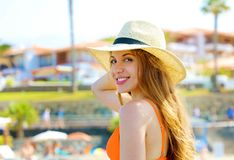 Closeup portrait of attractive blonde girl with long hair and hat posing on the beach. Beautiful bikini woman smiles to the camera. In her summer holidays royalty free stock photography