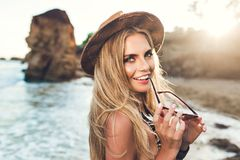 Closeup portrait of attractive blonde girl with long hair posing on rocky beach. She wears bikini, hat. She holds royalty free stock image