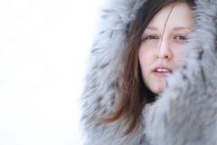 Closeup portrait of attractive brunette in a grey fur hoddie Royalty Free Stock Photo
