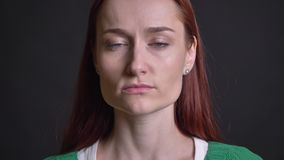 Closeup portrait of attractive caucasian female turning and looking straight at camera with neutral facial expression.  stock video