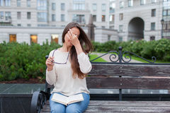 Closeup portrait of attractive female with eyeglasses in hand. Poor young girl has issues with vision. She rubs her nose and eyes. Out of fatigue. A student royalty free stock photo