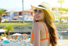 Closeup portrait of attractive girl with long hair posing on the beach. Beautiful bikini woman smiles to the camera in her summer. Holidays with sunglasses and stock photo