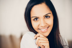 Closeup portrait of attractive indian young woman smiling at home royalty free stock photography