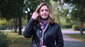 Closeup portrait of attractive young woman in autumn Park. girl in jacket and scarf.  stock video footage