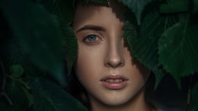 Closeup portrait of attractive young woman. Face looking through leaves. Closeup portrait of attractive young woman. Face looking through green leaves Royalty Free Stock Images