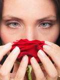 Closeup portrait of attractive young woman holding a red rose Royalty Free Stock Image