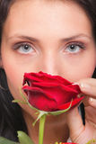 Closeup portrait of attractive young woman holding a red rose Stock Photos