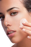 Moisturizer Cream. A woman applying makeup or moisturizer cream or balm on her cheek Stock Photography