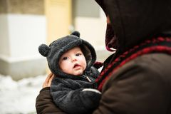 Closeup portrait of baby dressed in a bear costume. Closeup portrait of baby in a red carrier wear by his mother stock photos