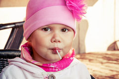 Closeup portrait of baby girl eating lollipop Stock Images