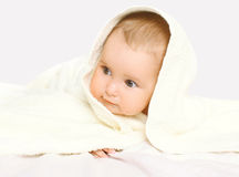 Closeup portrait of baby under towel on the bed Stock Photography