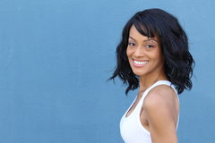 Closeup portrait of beautiful African American woman smiling in white bra showing her ample cleavage, over blue background Royalty Free Stock Photography
