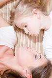 Closeup portrait of beautiful attractive woman with child blond girl lying face to face kiss Stock Image