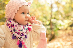 Closeup portrait of beautiful baby girl wearing stylish hat and cozy sweater. Outdoors spring, autumn photo. Stock Photo
