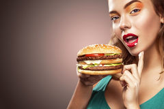 Closeup portrait. Beautiful blond young woman having fun eating big burger. Advertisment for cafe. Young woman eating big french hot-dog on Oktoberfest holiday stock images