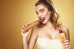 Closeup portrait. Beautiful blond young woman having fun eating french hot dog on Oktoberfest holiday. Royalty Free Stock Photography