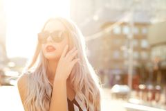 Closeup portrait of beautiful blonde girl wearing glasses, walking at the city in sunny evening.Space for text stock image