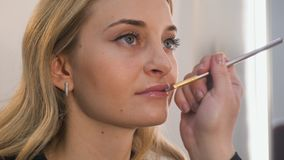 Closeup portrait of beautiful blonde woman doing make-up on her lips. stock photos