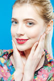 Closeup Portrait of Beautiful Blonde Woman with Ponytail and Perfect Skin Wearing Colorful Shirt on Blue Background. Portrait of Beautiful Blonde Woman with Stock Images