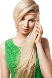 Portrait of beautiful blonde woman. Closeup portrait of a beautiful blonde young woman with hair on her face and hand next to her had, looking at camera Royalty Free Stock Photography
