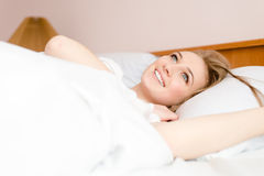 Closeup portrait of beautiful blonde young woman having fun happy smiling lying in white bed Royalty Free Stock Image