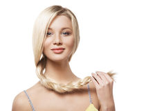 Young woman keeping braid with her hand. Closeup portrait of a beautiful blonde young woman keeping her braid with the hand Royalty Free Stock Images