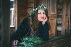 Closeup portrait of beautiful brunette girl in a wreath on a wooden background traditional Ukrainian or Russian house. Royalty Free Stock Images