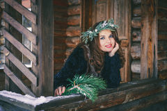 Closeup portrait of beautiful brunette girl in a wreath on a wooden background traditional Ukrainian or Russian house. Stock Image