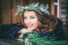 Closeup portrait of beautiful brunette girl in a wreath on a wooden background traditional Ukrainian or Russian house. Stock Images