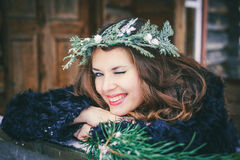 Closeup portrait of beautiful brunette girl in a wreath on a wooden background traditional Ukrainian or Russian house. Royalty Free Stock Photography
