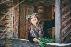Closeup portrait of beautiful brunette girl in a wreath on a wooden background traditional Ukrainian or Russian house. Royalty Free Stock Image