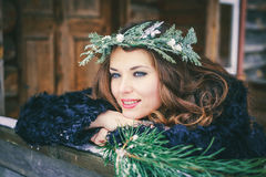Closeup portrait of beautiful brunette girl in a wreath on a wooden background traditional Ukrainian or Russian house. Royalty Free Stock Photos