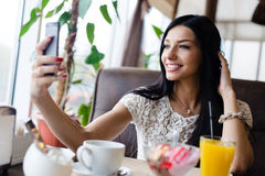 Closeup portrait of beautiful brunette young woman sitting making selfie or selfy on her mobile having fun happy smiling in cafe Stock Photos