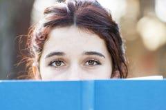 Closeup portrait of beautiful caucasian woman with blue book. Stock Photos
