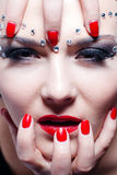 Pretty woman with bright red lips and manicure. Closeup Portrait of the beautiful elegant sensual girl with red lips & manicure, crystals makeup Stock Images