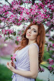 Closeup portrait of beautiful female  in fresh pink floral garden, warm sunset light, spring nature, vacation and Stock Photography