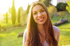 Closeup portrait of a beautiful friendly young brunette woman with nature on the background with flare light stock photography