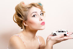 Closeup portrait of beautiful funny blond pinup girl with green eyes & curlers playing with car in the hands Stock Photography