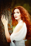 Closeup portrait of a beautiful ginger woman near the tree Royalty Free Stock Images