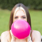 Closeup portrait of beautiful girl inflating balloon, outdoor. Portrait of girl inflating balloon Royalty Free Stock Photography