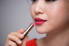 Closeup portrait of beautiful girl putting on red lipstick Royalty Free Stock Images